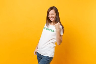 Portrait of happy overjoyed excited woman in white t-shirt with written inscription green title volunteer isolated on yellow background. Voluntary free assistance help, charity grace work concept