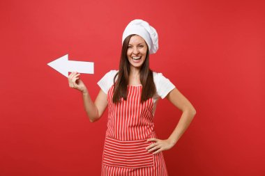 Housewife female chef cook or baker in striped apron, white t-shirt, toque chefs hat isolated on red wall background. Smiling fun housekeeper woman showing side with arrow. Mock up copy space concept