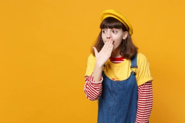Amazed girl teenager in french beret, denim sundress covering mouth with hand looking aside isolated on yellow wall background in studio. People sincere emotions lifestyle concept. Mock up copy space