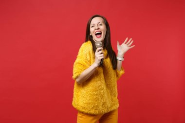 Pretty funny young woman in yellow fur sweater spreading hands s