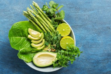 Detox Buddha bowl with avocado, asparagus, micro greens, lime, lettuce, basil and mint.Dietary food. Blue rustic background, top view