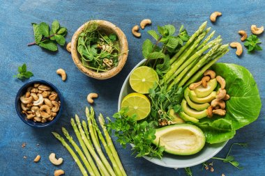 Avocado, asparagus, micro greens, lime, mint,basil, lettuce and cashew nuts. Detox bowl buddha. Blue rustic background, top view. Clean, wholesome food
