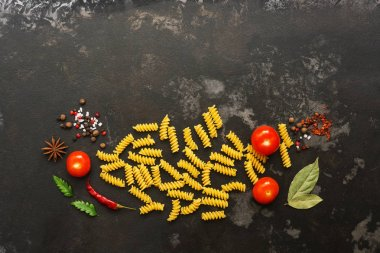 Uncooked fusilli pasta on a black stone background with spices and cherry tomatoes. Top view, copy space, flat lay
