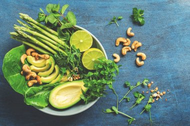 A bowl of green vegan salad with asparagus, avocado, lettuce, basil, mint, microgreen, lime and cashew nuts, blue rustic background. The concept of dietary vegetarian food. Top view