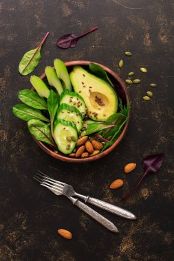 Healthy green salad with avocado, chard leaves, cucumber, celery, pumpkin seeds, flax and nuts.