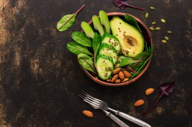 Healthy green salad with avocado, chard leaves, cucumber, celery, pumpkin seeds, flax and nuts. Top view