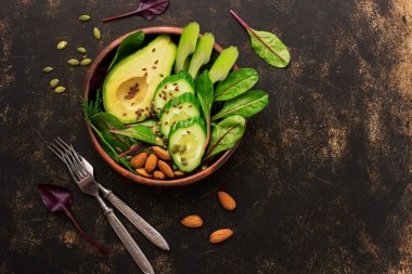 Healthy green salad with avocado, chard leaves, cucumber, celery, pumpkin seeds, flax and nuts. Top view.