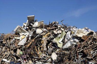 Huge pile of scrap metal junk garbage with blue sky background