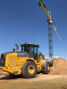 Construction site with bulldozer and crane. Copy space area in blue sky.