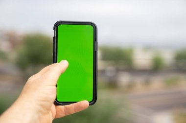 Man holding green screen smart phone with blurred outdoor background.
