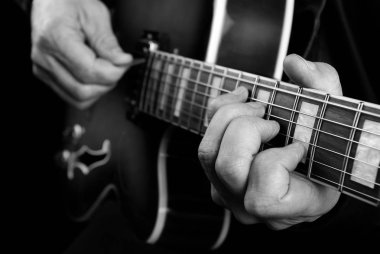 Guitarist hands and guitar close up. playing electric guitar. play the guitar. black and white.