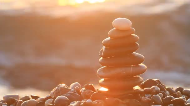 Pyramid of pebbles with sunrise on the sea splashes