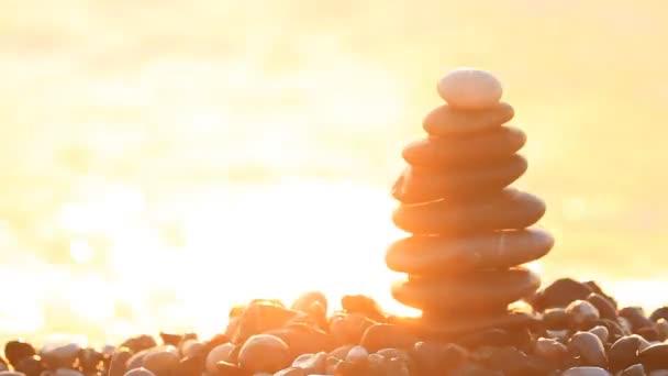Vlny se zde lámou pyramidu ze oblázky při východu slunce