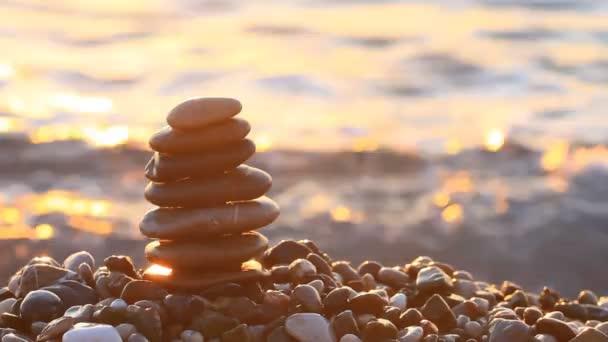 Pyramida z oblázků při východu slunce na moři.