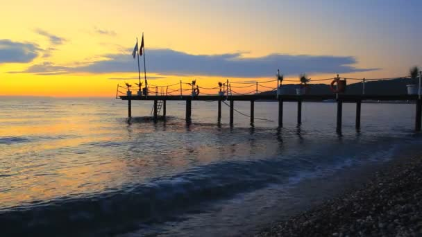 Silhouette of a pier with flag at sunrise on the sea in Kemer, Turkey