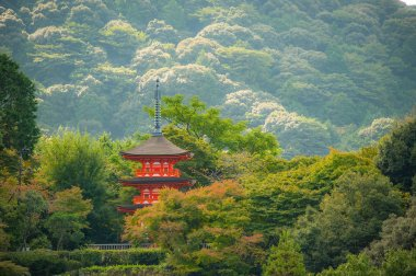 Beautiful red pagoda at Kiyomizu-dera Temple in Kyoto, Japan. A view of a three story pagoda stands in nature surrounded with sea of trees.