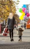 Fotografie Frau und Kind mit roten Einkaufstasche und Luftballons, gehen auf der Straße
