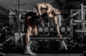 Photo guy bodybuilder, perform exercise with dumbbell on broadest muscle of a back, in dark gym