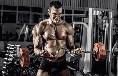 guy bodybuilder, perform exercise with weights barbell, in gym