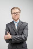 függőleges portré egy férfi üzletember vagy irodai dolgozó szemüvegben, álljon pózban - kéz a zsebben, szürke háttér