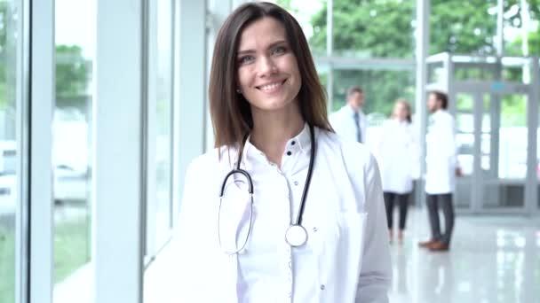 Glückliche junge Ärztin in weißem Arztkittel und Stethoskop, die in die Kamera blickt. Lächelnde Ärztin posiert im Krankenhausbüro.