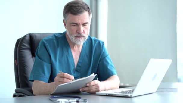 Qualified serious male therapist doing online research, reading news, making notes in medical journal. Focused old doctor physician using laptop at office desk