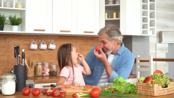 Šťastný táta a malá dcera vaří společně, smát se baví v kuchyni