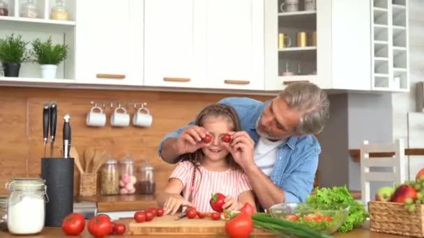 Boldog apa és lánya főzés együtt, nevetés szórakozás a konyhában