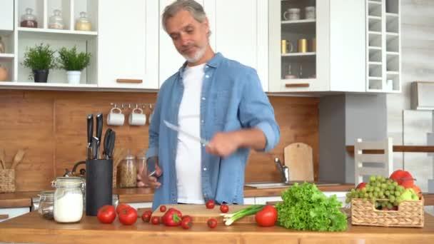 Muž připravuje vaření masa v kuchyni, ruce broušení nůž.