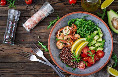 Delicious healthy Buddha bowl with shrimps, tomato, avocado, quinoa, lemon and arugula on the wooden table. Healthy food. Top view