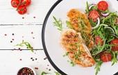 Grilované kuřecí řízky a čerstvý zeleninový salát z rajčat, červenou cibulí a rukolou. Salát kuřecí maso. Zdravé jídlo.