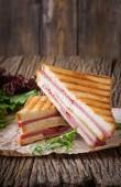Club sandwich - panino con prosciutto e formaggio su fondo di legno. Alimento di picnic.