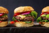 Fotografie Hamburger s hovězím masem burger a čerstvá zelenina na tmavém pozadí. Chutné jídlo