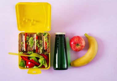 Healthy school lunch box with beef sandwich and fresh vegetables, bottle of water and fruits on pink background. Top view. Flat lay