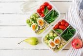 Vegetariánské jídlo přípravka kontejnery s vejci, kapustičkami, fazolovými lusky a rajčaty na bílém pozadí dřevěná