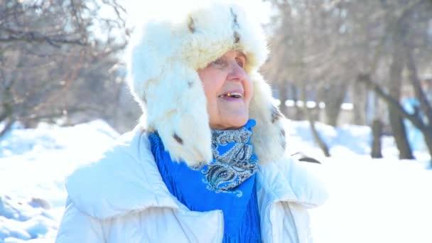 Porträt einer glücklichen, lächelnden Großmutter. Blick in die Kamera. kaukasische Seniorin im kalten Winter. Modedame draußen. Oma mit blauen Augen in Fellmütze. Fröhliche, lustige Senioren genießen Schnee