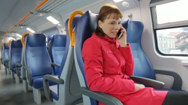 Woman talking on mobile phone in train