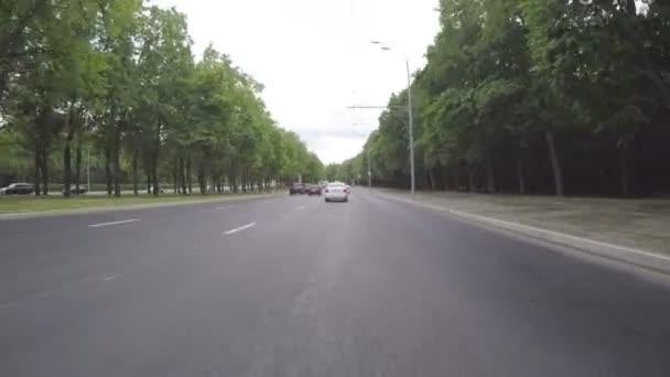 Auto jezdí na město, ulici, která vede přes park. První osoba pohled z karoserie