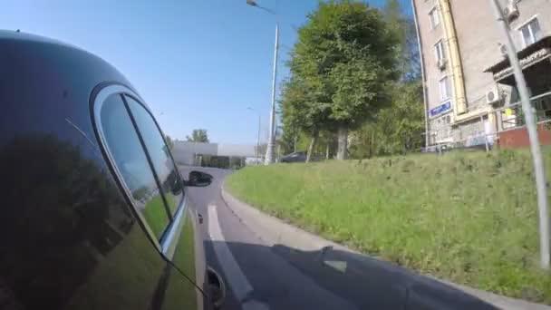 Das Auto bewegt sich an einem sonnigen Sommertag die Stadtstraße entlang. Seitenansicht der Karosserie.