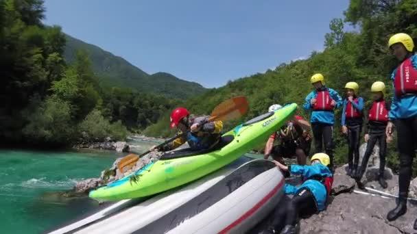 Adventure POV shot of green kayak sliding down rafting boat on Soca river, Slovenia.