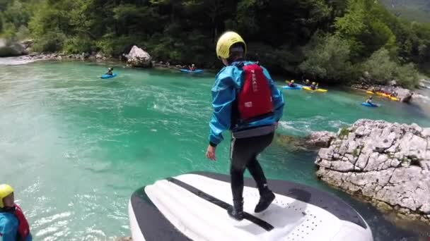 Adventure POV shot of young girl running and sliding down rafting boat on Soca river, Slovenia.
