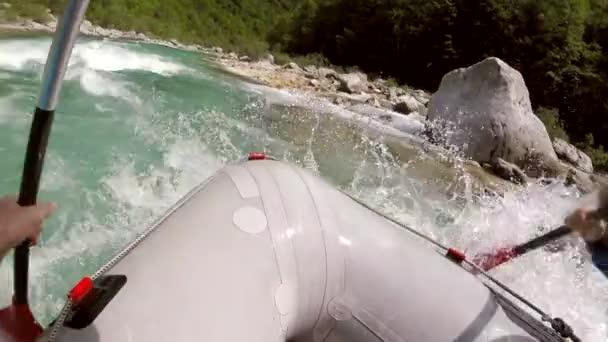 Adventure POV shot of front of people rafting boat in Soca river in Slovenia.