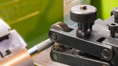 Two wheel knurling tools when working on a lathe. Sharp cutting wheels for grooving. Machining of a metal workpiece clamped in the machine-tool chuck. Idea of industry, engineering, metalwork.