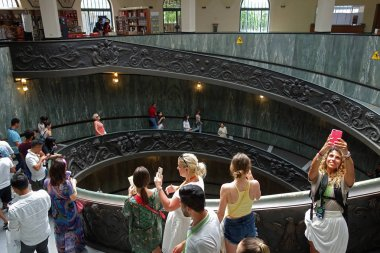 VATICAN, VATICAN CITY - 14 JULY 2018: People descending the modern 'Bramante' spiral stairs of the Vatican Museums, designed by Giuseppe Momo in 1932