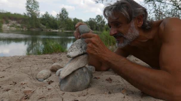 muž dělá kamenné hromady podél řeky