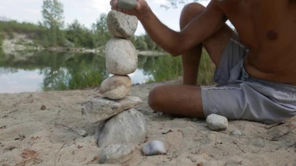 Starší muž dělá hromady kamene podél řeky