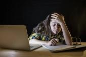 Überarbeitete Studentin im karierten Hemd hält Kopf, während sie am Laptop arbeitet und versucht nicht einzuschlafen