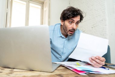 young angry and worried man working with laptop at home looking at bills and paying bills in home finance concept