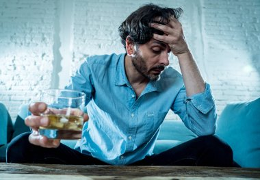 drunk alcoholic lain business man drinking whiskey from the bottle and glass depressed wasted and sad at home couch in alcohol abuse and alcoholism concept