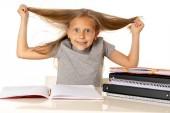 dolce giovane piccola Scolara tirando i capelli disperata in stress mentre seduto sul banco di scuola, fare i compiti stanco ed esaurito isolato su sfondo bianco nel concetto di formazione